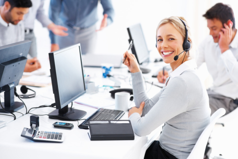 Portrait of happy female customer service executive looking at you and smiling